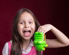 Young Asian American girl with green crcodile Stock Photos
