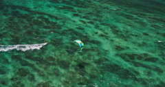 Aerial view of kitesurfer gliding across blue ocean Stock Footage