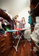 housewife looking at not ironed clothes at wardrobe - stock photo