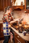 housewife cooking soup in saucepan - stock photo
