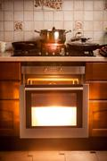 Hot oven and pan boiling on stove at kitchen Stock Photos