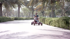 Father and son riding pedal go kart and giving high five at park. Stock Footage