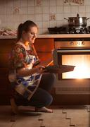 housewife sitting next to oven and holding pan near hot oven - stock photo