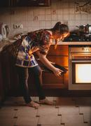 Housewife holding cookies on pan near oven Stock Photos