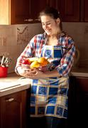 Woman wearing apron holding fresh bowl with fruits Stock Photos