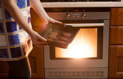 photo of woman putting cookies in oven - stock photo