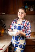 portrait of beautiful woman holding bowl with flour - stock photo