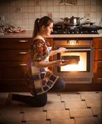 Brunette woman holding pan with cookies near oven Stock Photos