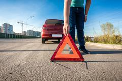 Man placing red triangle sing on road after car crash Kuvituskuvat
