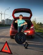 man sitting on car trunk and holding foot on spare wheel - stock photo