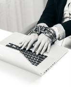 closeup photo of woman locked to laptop by chain - stock photo