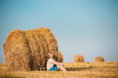 Beautiful Plus Size Young Woman In Shirt Sit Near Hay Bales In S - stock photo