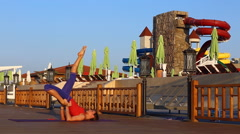 Pretty woman doing yoga on the beach. Sporty woman sitting in yoga position, sea Stock Footage