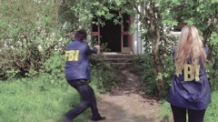 Two FBI Agents running into a abandoned with drawed guns - stock footage