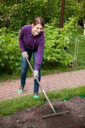 beautiful woman working with rake on garden bed - stock photo