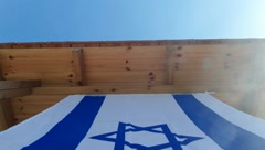 Israeli national flag fluttering in the balcony of a house. Stock Footage