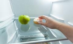 hand choosing donut instead of apple lying in fridge - stock photo