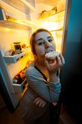 portrait of woman biting donut at night near fridge - stock photo
