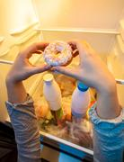 hands taking big donut from top shelf of fridge - stock photo