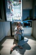 woman sitting near refrigerator at late night - stock photo
