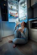 Woman sitting on floor at kitchen and having late dinner Stock Photos