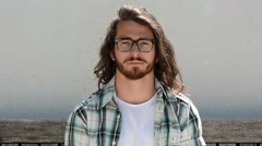 Young man portrait. Middle twenties. Long hair, blue  eyes and glasses - stock footage