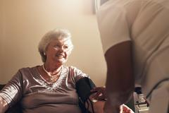 Elderly woman getting routine check from a female doctor - stock photo