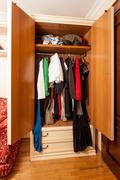 photo of wardrobe with clothes on hangers in it - stock photo