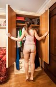 woman in lingerie looking at open wardrobe - stock photo