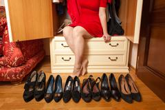 Woman sitting in wardrobe with lots of shoes Stock Photos