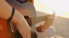 Young boy plays guitar at sunset Stock Footage