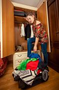 Brunette woman packing clothes in big suitcase Kuvituskuvat