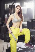 Nice sexy woman mechanic holding wrench. Girl weared in yellow work overalls and Stock Photos