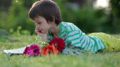Cute little preschool boy, reading a book in garden, late spring afternoon - stock footage