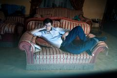 man lying on sofa and watching TV at night - stock photo