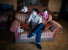 two daughters disturbing father while watching TV at night - stock photo