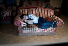 man sleeping on sofa at night near TV - stock photo