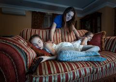 mother waking up two daughter fell asleep at night while watching TV - stock photo