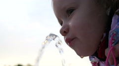 Little child kid girl drinking water from a drinking fountain in the park - stock footage