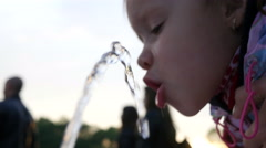 Little child kid girl drinking water from a drinking fountain in the park Stock Footage