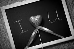 Monochrome photo of declaration of love written on blackboard - stock photo
