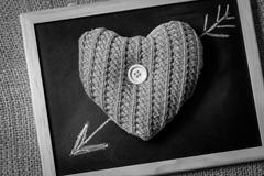 Monochrome photo of drawn by chalk arrow going through knitted heart - stock photo