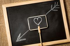 Photo of heart with arrow drawn by chalk on blackboard Stock Photos