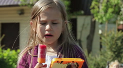 The little girl eating ice cream on a stick and looking in a smartphone Portrait Stock Footage