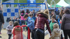 Children have fun playing playground - swing sets and merry-go-rounds Stock Footage