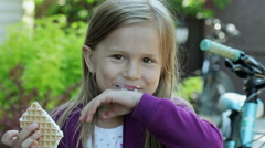The little girl eating vanilla ice cream and looking at camera. Portrait. Stock Footage