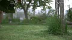 man mows the grass trimmer slow motion - stock footage
