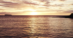 Aerial view flying over calm ocean into beautiful sunset Stock Footage