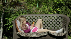 Pleasant little girl lying on the sofa in the garden and looking in a smartphone Stock Footage