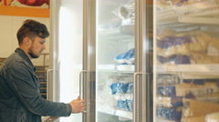 Handsome Man Shopping In A Supermarket, Taking Frozen Food From Freezer - stock footage